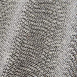 Eine Detailaufnahme von glattgestrickter grauer Wolle