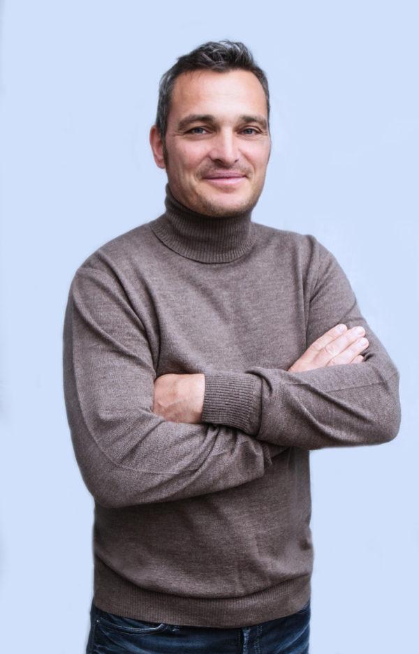 Ein Mann trägt einen nougatfarbenen Merinopullover mit Rollkragen.