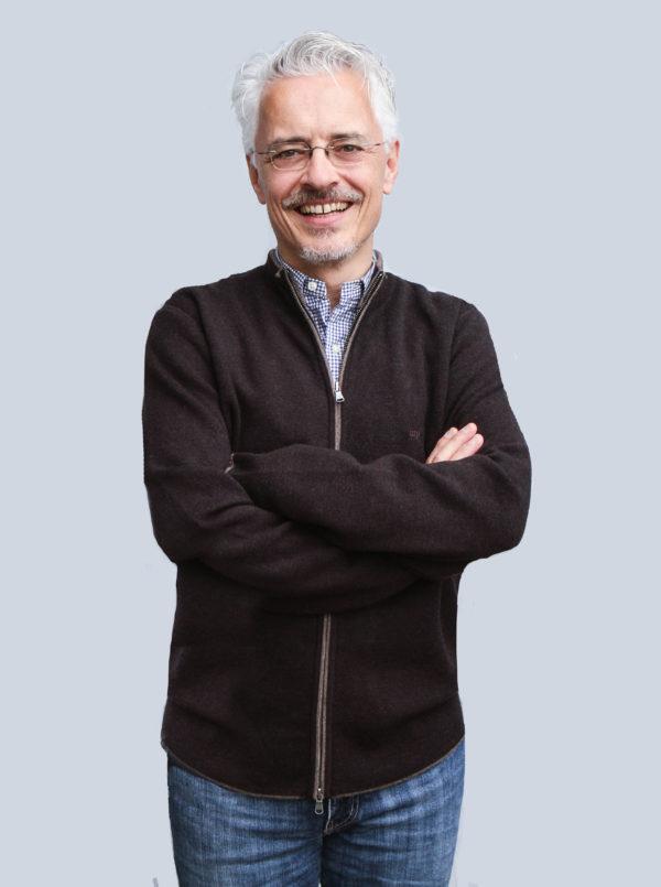 Das männliche Modell trägt eine dunkelbraune Strickjacke mit Reißverschluss.