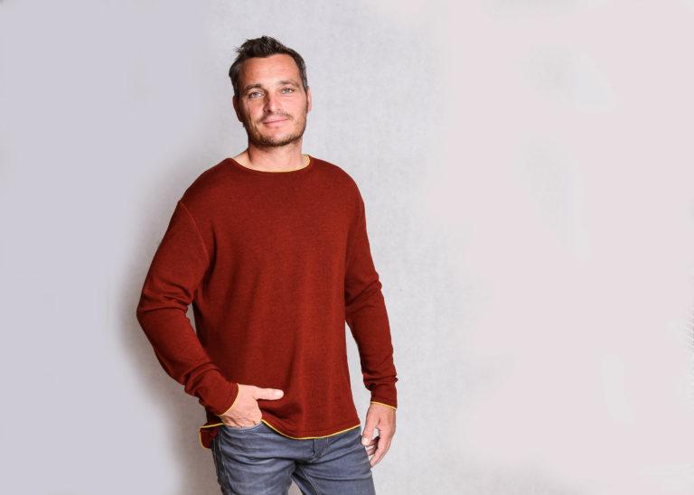 Das männliche Modell trägt einen ziegelfarbenen Pullover aus Merinowolle mit lemonfarbenen Kontraststreifen.