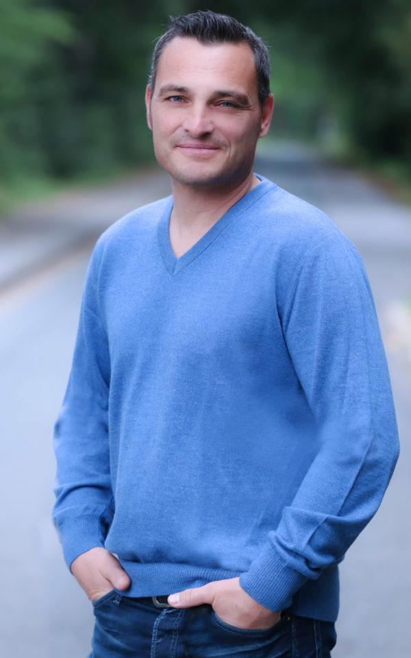 Das männliche Modell trägt einen jeansfarbenen Pullover mit V-Auschnitt.