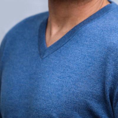 Detailaufnahme vom Brustbereich eines Mannes, der einen jeansfarbenen Pullover mit V-Auschnitt trägt.