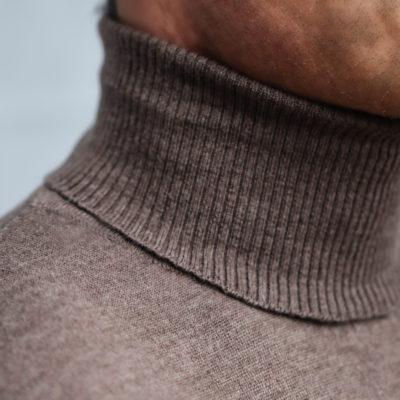Detailaufnahme vom Halsbereich eines Mannes. Er trägt einen nougatfarbenen Rollkragenpullover