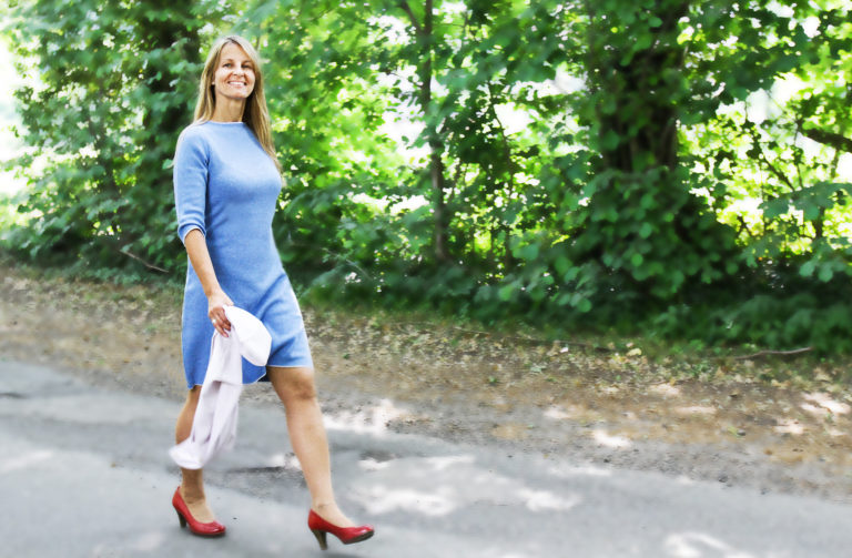 Das weibliche Modell spaziert in einem hellblauen Strickkleid an einer von Bäumen gesäumten Straße.