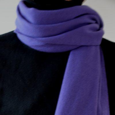 Ein violetter Kaschmirschal locker um den Hals geschlagen.