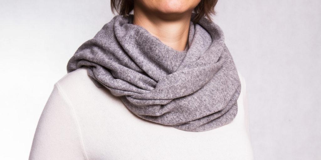 Eine Frau trägt einen silbergrauen Kaschmirschal kurz um den Hals gewickelt.