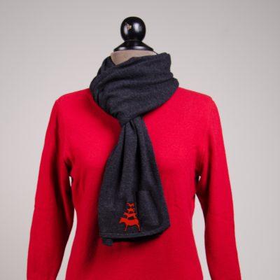 Eine Kleiderpuppe trägt einen roten Pullover. Um den Hals in Schlaufe geschlagen ist ein anthrazirfarbener Schal mit aufgestickten Bremer Stadtmusikanten in rot.