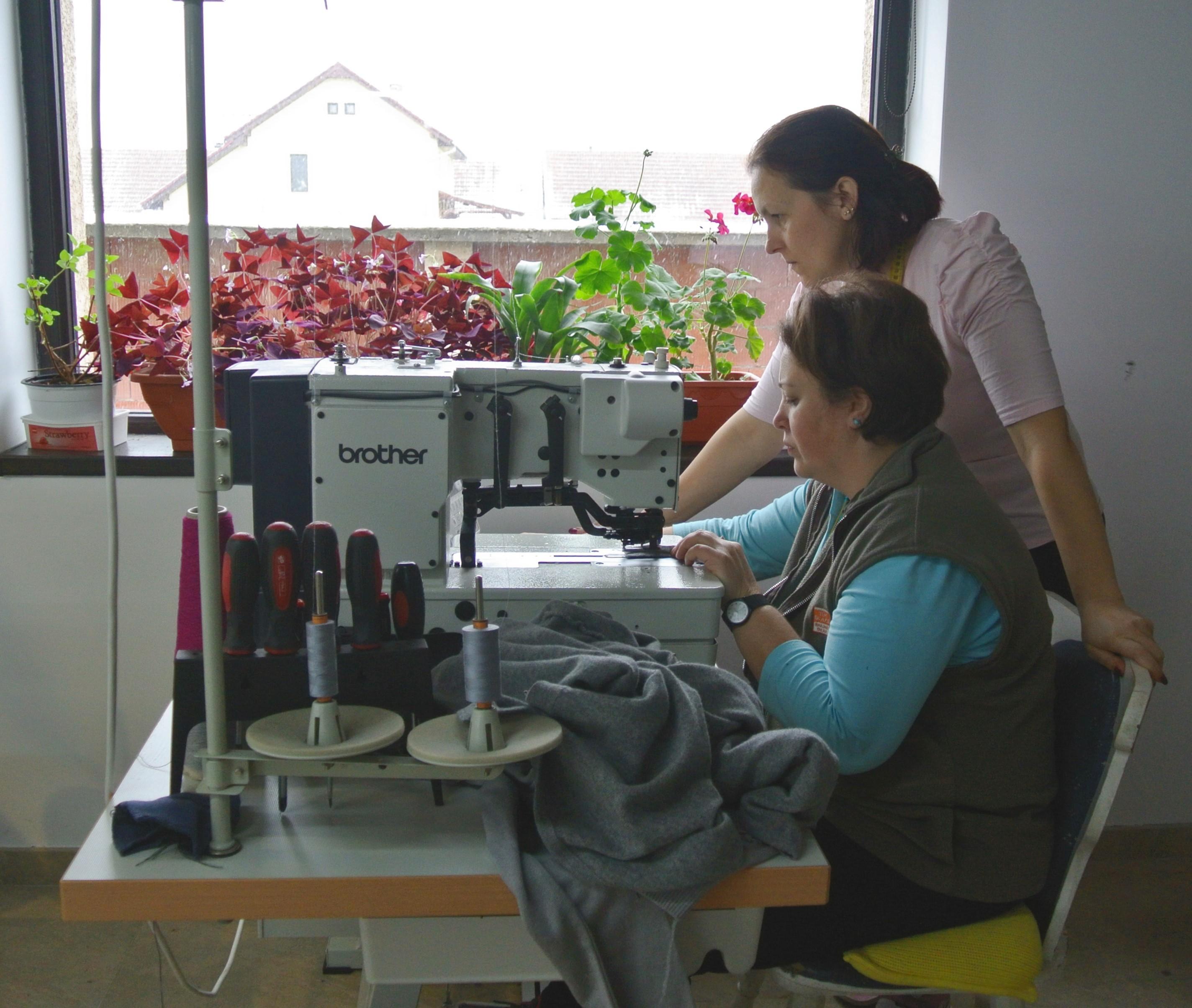 Zwei Frauen an einem Nähmaschinentisch.